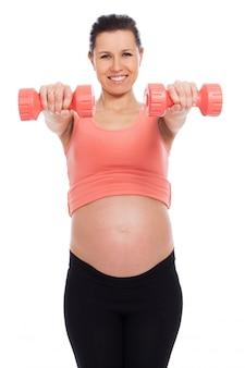 Schwangere frau, die mit dummköpfen ausarbeitet