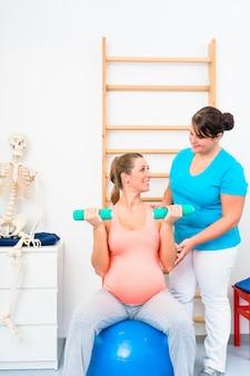 Schwangere frau, die mit dummköpfen in der physiotherapie ausarbeitet