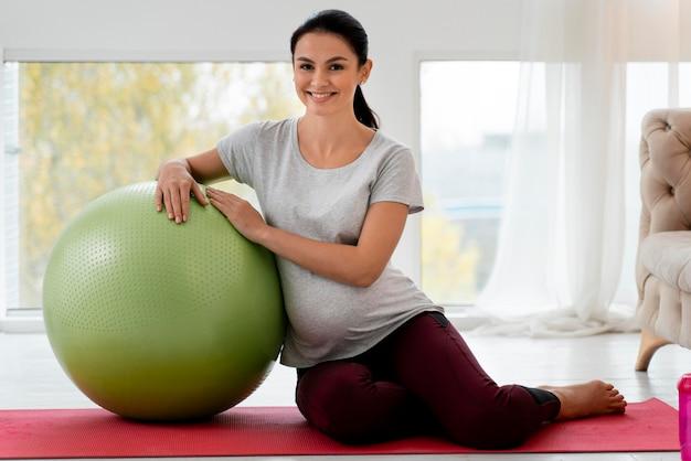 Schwangere frau, die mit fitnessball trainiert