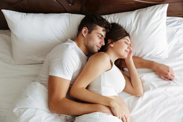 Schwangere frau, die mit ihrem ehemann im bett schläft