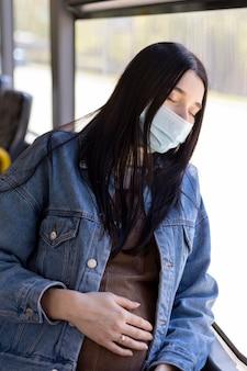 Schwangere frau, die mit maske reist