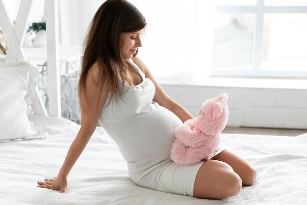 Schwangere frau, die mit teddybären spielt
