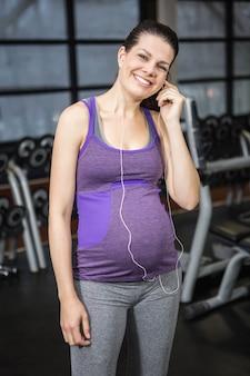 Schwangere frau, die musik an der turnhalle hört