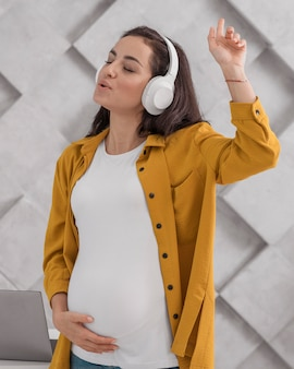 Schwangere frau, die musik auf kopfhörern genießt