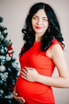 Schwangere frau, die nahe weihnachtsbaum zu hause aufwirft. frohe weihnachten und schöne feiertage! konzept für schwangerschaft, urlaub, menschen und erwartung.