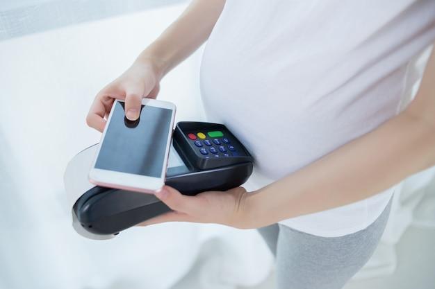 Schwangere frau, die online mit anschluss und telefon kauft