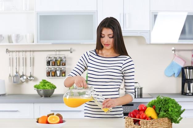 Schwangere frau, die orangensaft in glas in der küche gießt