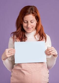 Schwangere frau, die papier mit baby in der ofennachricht hält