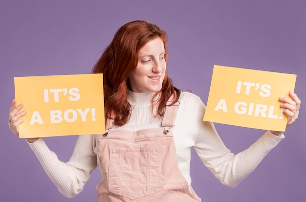 Schwangere frau, die papier mit babygeschlecht hält