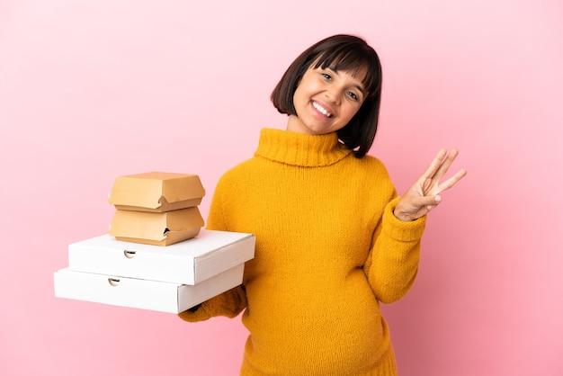 Schwangere frau, die pizza und burger einzeln auf rosafarbenem hintergrund hält, glücklich und mit den fingern drei zählend