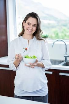 Schwangere frau, die salat in der küche isst
