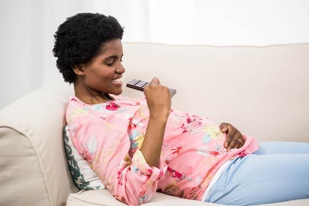 Schwangere frau, die schokolade auf couch isst
