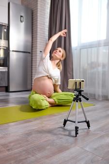 Schwangere frau, die sich zu hause ausdehnt und auf dem smartphone aufzeichnet