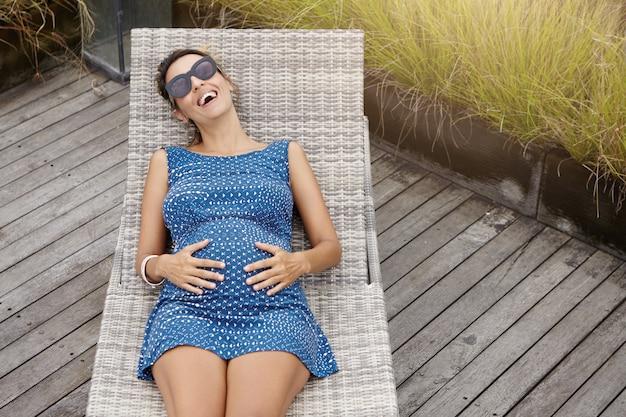 Schwangere frau, die stilvolle sonnenbrille und blaues sommerkleid trägt, das auf sonnenliege liegt, hände auf ihrem bauch hält und glücklich lacht, ruhige und friedliche tage ihrer schwangerschaft im freien genießt