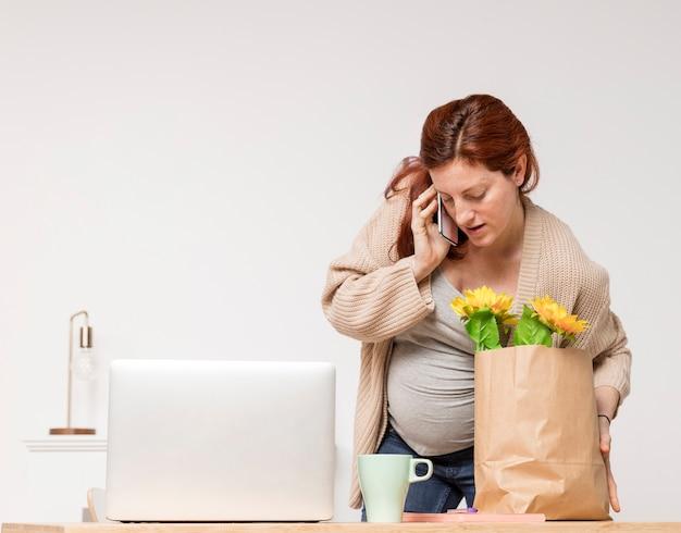 Schwangere frau, die über telefon spricht