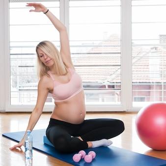 Schwangere frau, die übung in der turnhalle tut