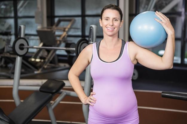 Schwangere frau, die übungsball an der turnhalle hält