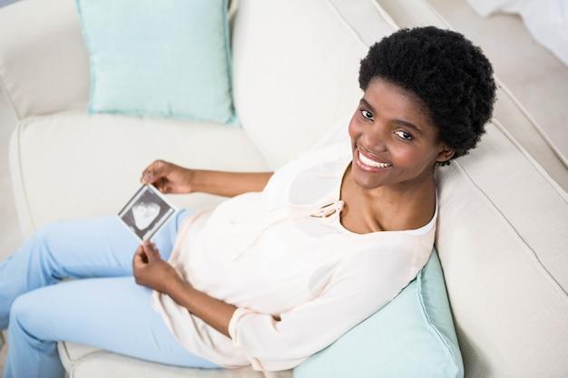 Schwangere frau, die ultraschallscan auf couch hält
