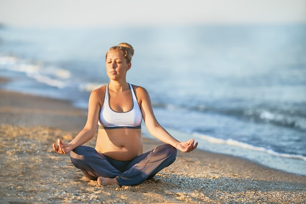 Schwangere frau, die yoga am strand tut. sanftes licht. schönes mädchen mit einem badeanzug. meer. sie entspannt yoga.