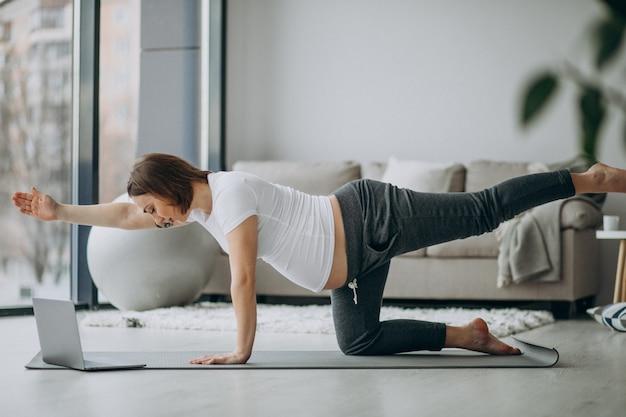 Schwangere frau, die yoga zu hause ausübt