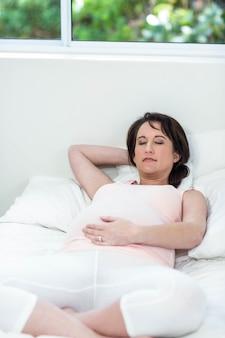 Schwangere frau, die zu hause auf ihrem bett stillsteht