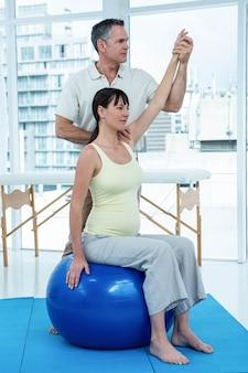 Schwangere frau, die zu hause mit physiotherapeuten auf übungsball trainiert