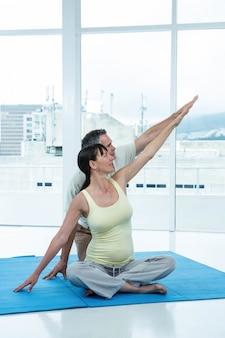 Schwangere frau, die zu hause mit physiotherapeuten trainiert