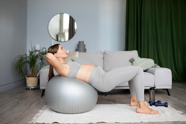 Schwangere frau, die zu hause trainiert