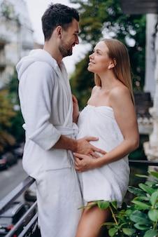 Schwangere frau eingewickelt im tuch auf balkon mit ehemann
