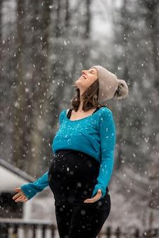 Schwangere frau genießt schneefall