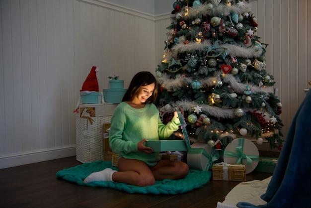 Schwangere frau glücklich zu hause nahe dem weihnachtsbaum während der weihnachtsfeier