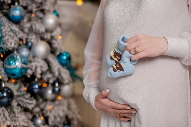 Schwangere frau hält babyschuhe. bauch mit booties aus der nähe.