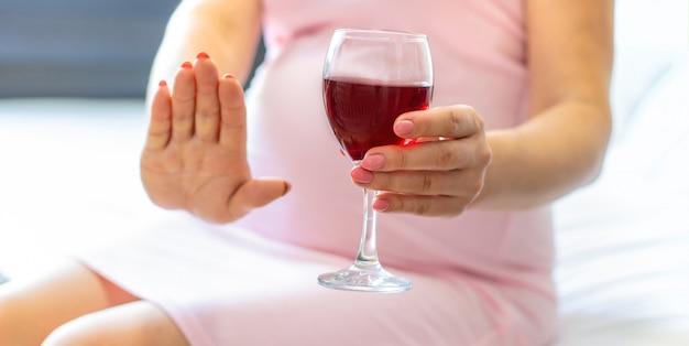 Schwangere frau hält ein glas wein