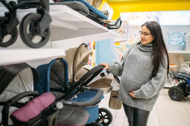 Schwangere frau im geschäft von waren für neugeborene. zukünftige mutter, die kinderwagen für ihr kind wählt