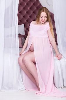 Schwangere frau im rosafarbenen kleid. mutterschaft, schwangerschaft