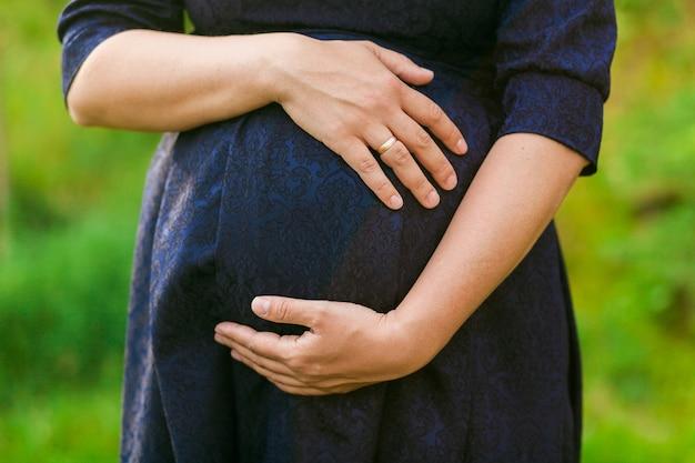 Schwangere frau im schwarzen kleid auf blured grünen gras hintergrund