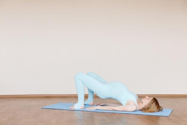 Schwangere frau im yogaanzug trainiert zu hause