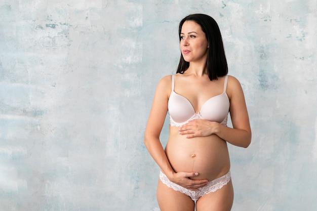 Schwangere frau in der unterwäsche mit exemplarplatz