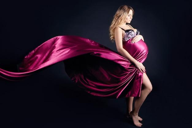 Schwangere frau in der wäsche auf schwarzem hintergrund