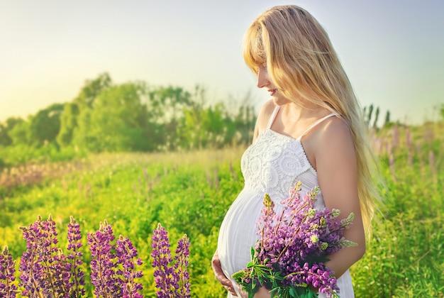 Schwangere frau in einem lupinenfeld