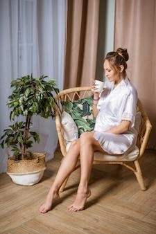 Schwangere frau in einem weißen kittel, sitzend auf einem stuhl mit einem becher in der hand