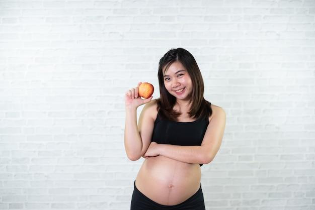 Schwangere frau in einem weißen kleid, das roten apfel anhält
