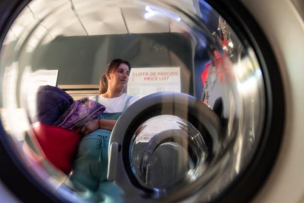 Schwangere frau in einer wäscherei. halten der zu waschenden kleidung in einem korb. künstlerische ansicht.