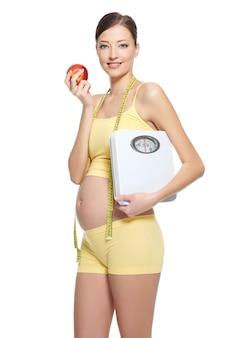 Schwangere frau in gelber sportlicher kleidung, die roten apfel und gewichtswaage auf weiß hält