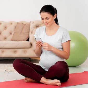 Schwangere frau in lotussitz, die ihr telefon überprüft