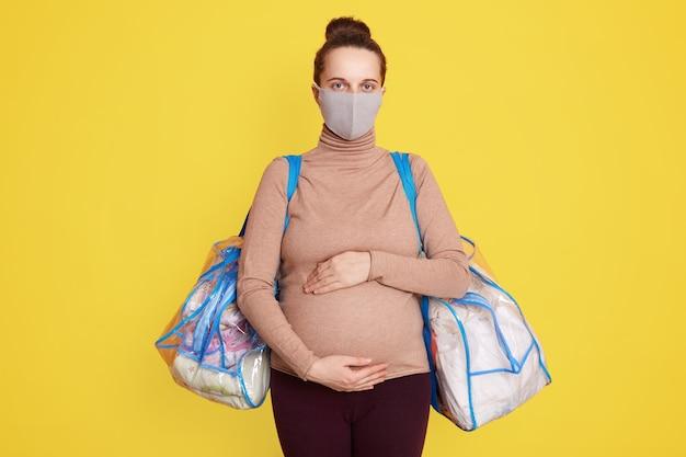 Schwangere frau in medizinischer gesichtsmaske gegen grippe und viren, die bereit sind, ins entbindungsheim zu gehen, kleidet sich lässig und hält zwei taschen mit sachen für die geburt.