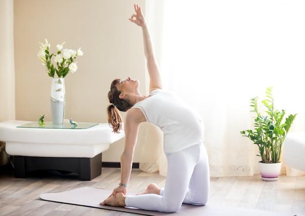 Schwangere frau macht ustrasana yoga pose zu hause