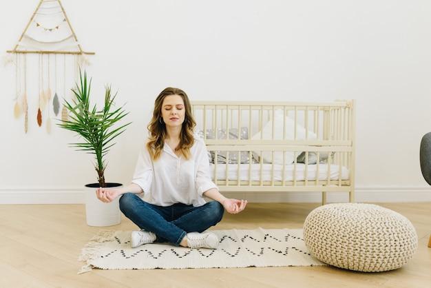 Schwangere frau meditiert und ist im kinderzimmer achtsam