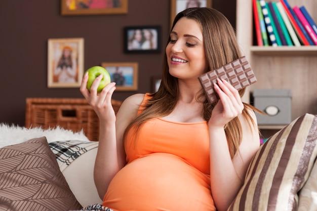 Schwangere frau mit apfel und schokolade