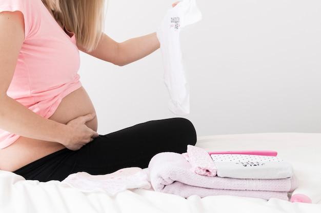 Schwangere frau mit babykleidung